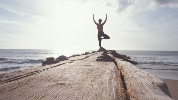 Woman in yoga pose on a pier
